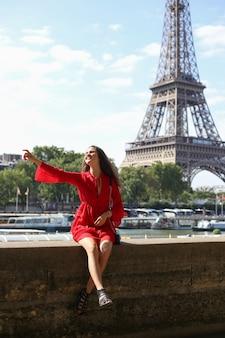 Dziewczyna w czerwonej sukience siedząc naprzeciwko wieży eiffla w paryżu