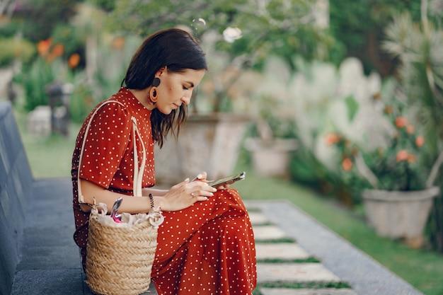 Dziewczyna w czerwonej sukience siedzi i używa telefonu
