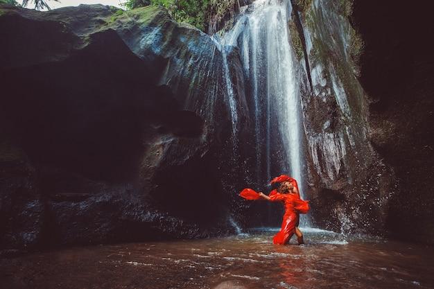 Dziewczyna w czerwonej sukience tańczy w wodospadzie.