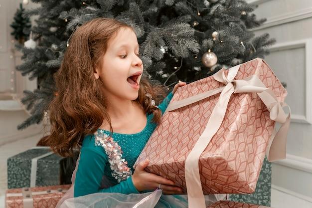 Dziewczyna w czerwonej sukience trzyma pudełko prezentów i raduje się