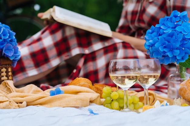 Dziewczyna w czerwonej sukience w kratkę i kapelusz siedzi na białej dzianiny koc piknikowy, czytanie książki i picie wina. letni piknik w słoneczny dzień z chlebem, owocami, bukietem kwiatów hortensji. selektywna ostrość