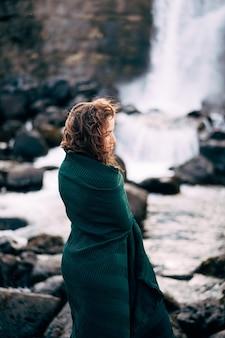 Dziewczyna w czerwonej sukience w pobliżu ehsaraurfoss falls ehsarau river national park tingwedlir sudurland