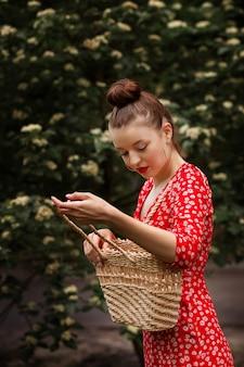 Dziewczyna w czerwonej sukience ze słomianą torbą w naturze w lecie