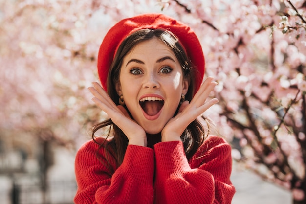 Dziewczyna w czerwonym berecie w radosnym szoku patrzy na aparat na tle sakury. zdziwiona zielonooka kobieta w swetrze pozuje w kwitnącym ogrodzie