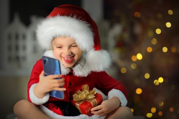 Dziewczyna w czerwonym garniturze i czapce mikołaja śmiejąca się głośno przez telefon z powodu prezentu na boże narodzenie