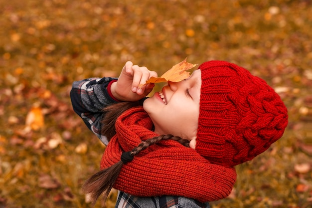 Dziewczyna w czerwonym kapeluszu wącha żółty opadły liść na tle jesiennej polany