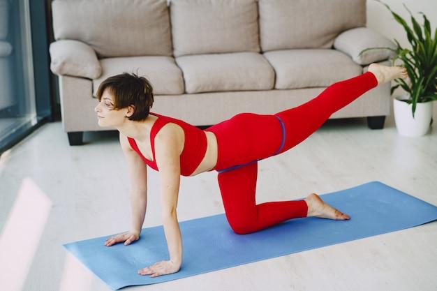 Dziewczyna w czerwonym sportowym mundurze ćwiczy joga w domu