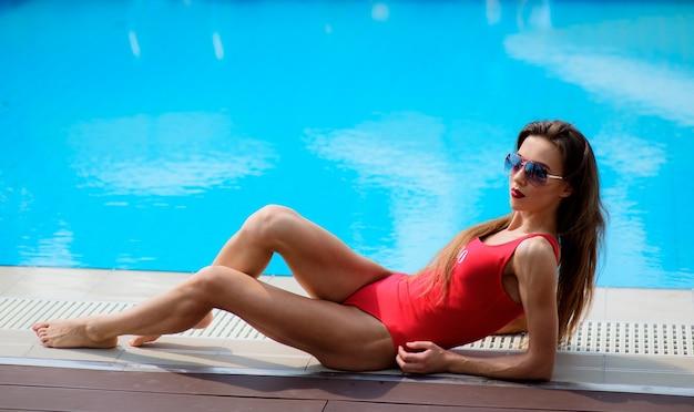 Dziewczyna w czerwonym strój kąpielowy leży przez niebieski basen