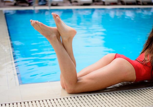 Dziewczyna w czerwonym strój kąpielowy w niebieskim basenie