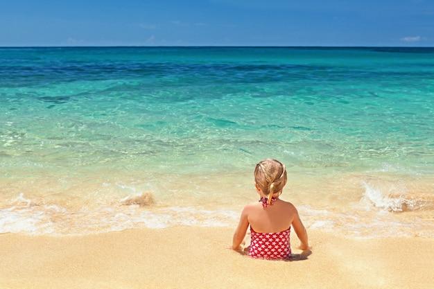 Dziewczyna w czerwonym stroju kąpielowym siedzi na krawędzi piaszczystej plaży