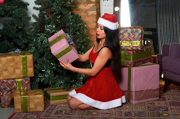 Dziewczyna w czerwonym stroju świątecznym z prezentami w dłoniach.