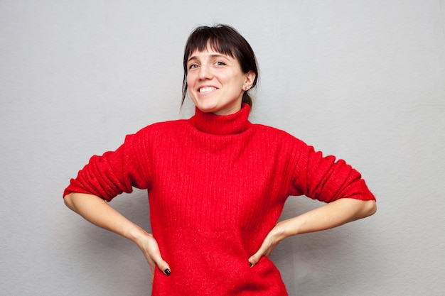 Dziewczyna w czerwonym swetrze na szarej ścianie