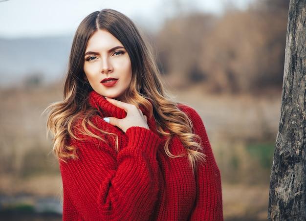 Dziewczyna w czerwonym swetrze w lesie