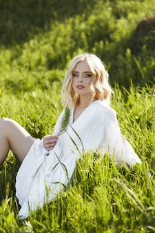 Dziewczyna w długiej białej sukni siedzi na trawie w polu. blondynki kobieta w słońcu w lekkiej sukni. dziewczyna odpoczywa i marzy, idealny letni makijaż na twarzy