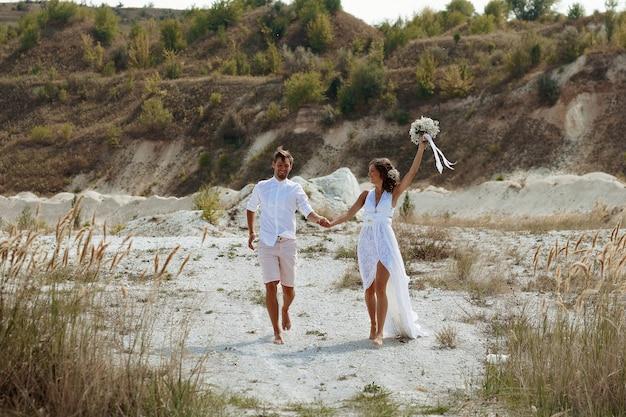 Dziewczyna w długiej białej sukni z kwiatami we włosach i mężczyzna w białej koszuli i szortach na tle białego plażowego piasku i suchej trawy