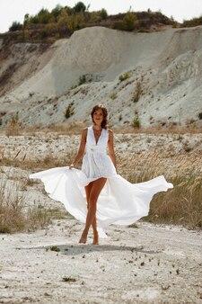 Dziewczyna w długiej białej sukni z kwiatami we włosach na tle białego piasku plaży i suchej trawy