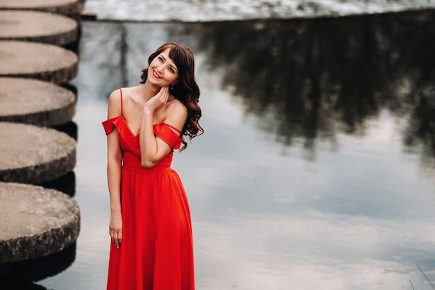 Dziewczyna w długiej czerwonej sukience w pobliżu jeziora w parku o zachodzie słońca.