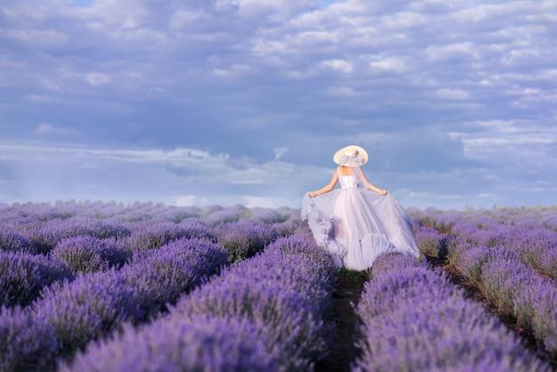 Dziewczyna w długiej sukni biegnie w lawendowym polu. panna młoda w lawendie. zdjęcie z tyłu.