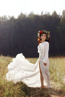 Dziewczyna w długiej sukni stoi na polu z wieńcem na głowie i bukietem kwiatów w dłoniach, piękną kobietą w promieniach wieczornego słońca jesienią