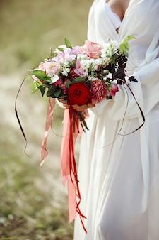 Dziewczyna w długiej sukni stoi na polu z wieńcem na głowie i bukietem kwiatów w dłoniach