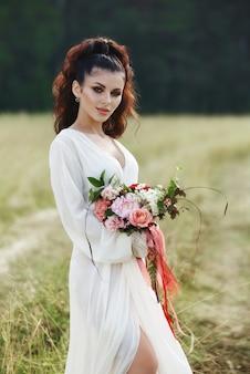 Dziewczyna w długiej sukni stoi w polu z wieńcem na głowie i bukietem kwiatów w dłoniach, piękna kobieta w promieniach wieczornego słońca jesienią w wiosce. życie na wsi i moda