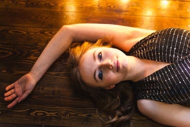 Dziewczyna w długiej wieczorowej sukni leży na podłodze w pobliżu świecących świateł