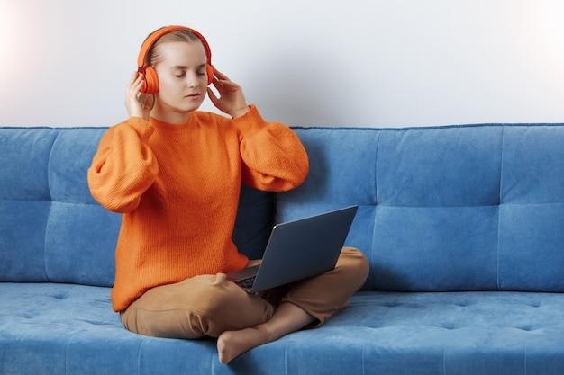 Dziewczyna w domu na kanapie słucha muzyki online