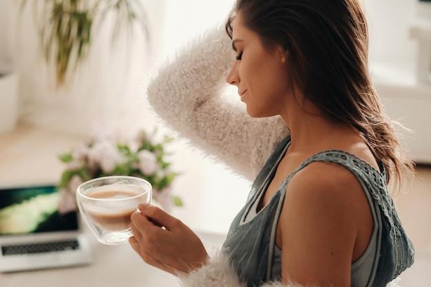 Dziewczyna w domu pije kawę i ogląda film