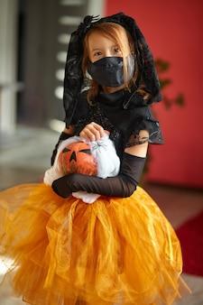 Dziewczyna w domu w kostiumie na halloween z dyniowym jackiem lub laurentem w rękach, dziecko ubrane w czarną maskę chroniącą przed koronawirusem, halloween w kwarantannie