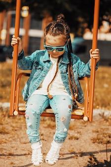 Dziewczyna w drelichu w ciemnych okularach huśta się na huśtawkach. zdjęcie wysokiej jakości