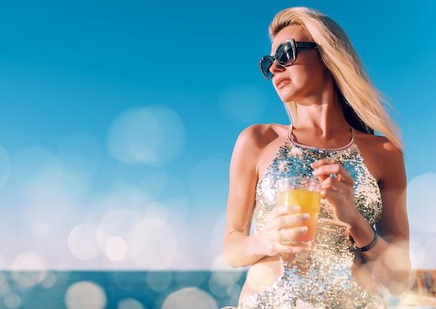 Dziewczyna w drogim kostiumie kąpielowym z koktajlem w dłoniach spędza wakacje przy basenie w ośrodku