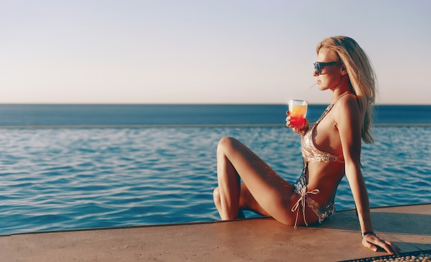 Dziewczyna w drogim kostiumie kąpielowym z koktajlem w rękach spędza wakacje przy basenie w kurorcie