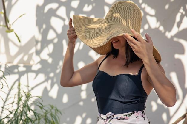 Dziewczyna w dużym słomkowym kapeluszu przed ścianą pokrytą kędzierzawym starym drzewem.