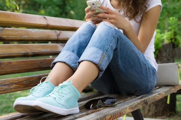 Dziewczyna w dżinsach siedzi na ławce w parku i za pomocą telefonu komórkowego
