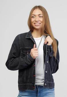 Dziewczyna w dżinsowej czarnej kurtce i niebieskich dżinsowych spodniach na białym tle.