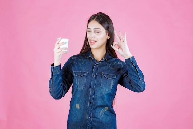 Dziewczyna w dżinsowej koszuli, kawie i ciesząc się smakiem