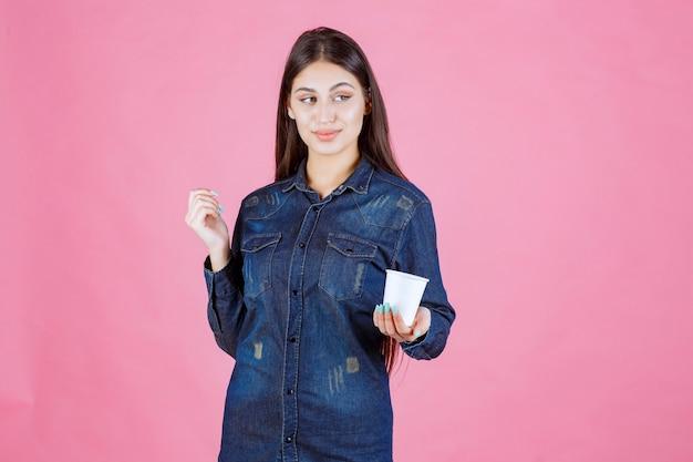 Dziewczyna w dżinsowej koszuli oferuje przyjacielowi filiżankę kawy