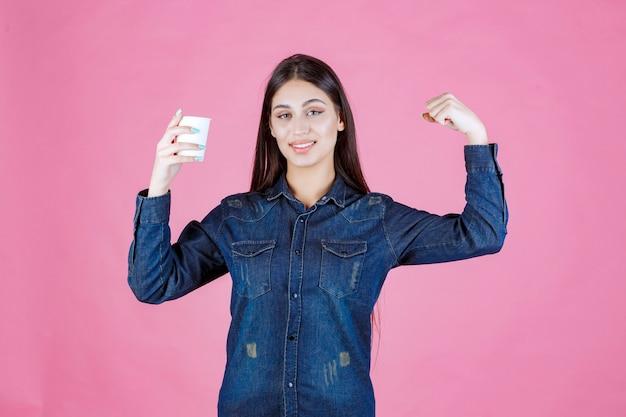 Dziewczyna w dżinsowej koszuli przy filiżance kawy i poczuciu siły