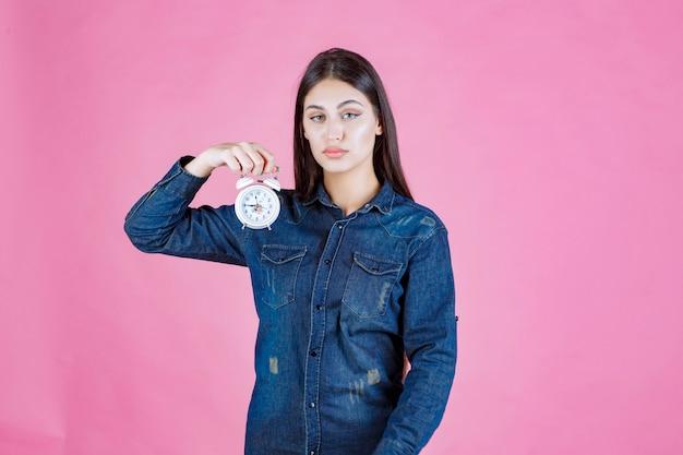 Dziewczyna w dżinsowej koszuli trzyma i promuje budzik