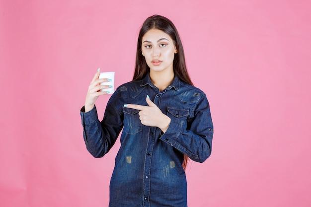 Dziewczyna w dżinsowej koszuli, trzymając filiżankę kawy i czuje się pozytywnie