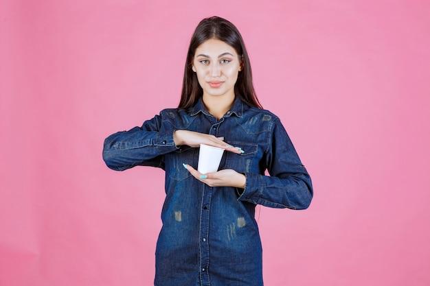 Dziewczyna w dżinsowej koszuli, trzymając filiżankę kawy między rękami