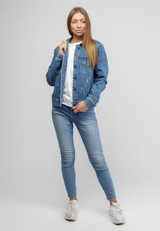 Dziewczyna w dżinsowej kurtce i niebieskich dżinsowych spodniach na białym tle