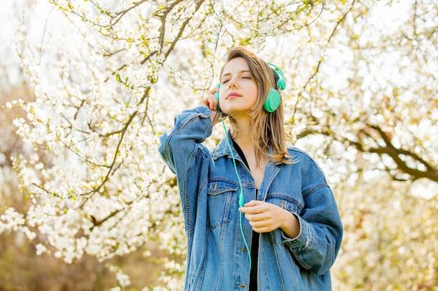 Dziewczyna w dżinsowej kurtce i słuchawkach stoi w pobliżu kwitnącego drzewa