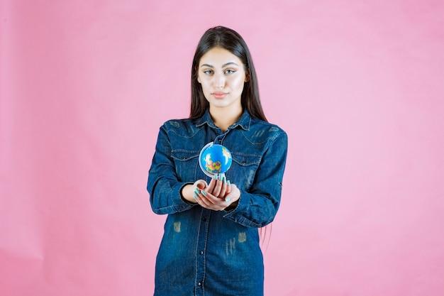 Dziewczyna w dżinsowej kurtce, oferując przyjaciółce swoją mini kulę ziemską