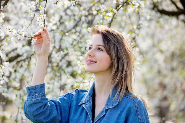 Dziewczyna w dżinsowej kurtce pozostaje blisko kwitnącego drzewa