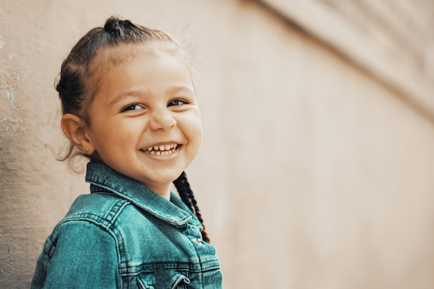 Dziewczyna w dżinsowej kurtce uśmiecha się stojąc pod ścianą. zdjęcie wysokiej jakości