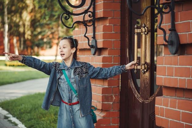 Dziewczyna w dżinsy ubrania w pobliżu starego budynku z czerwonej cegły