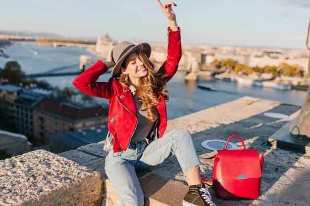 Dziewczyna w elegancki kapelusz i spodnie vintage śmieszne pozowanie na tle rzeki