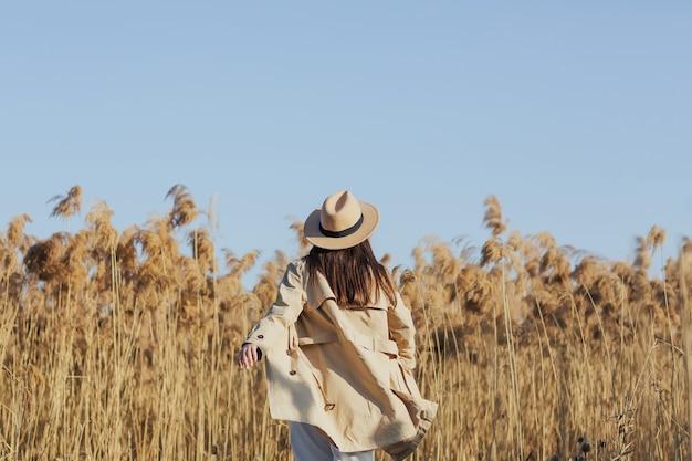 Dziewczyna w eleganckich ubraniach wiruje w polu z trzcinami