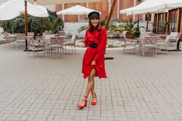 Dziewczyna w eleganckiej, czerwonej sukience z paskiem i butach na miejskim obcasie pokazuje smukłe nogi. pełnometrażowe zdjęcie w miejskiej kawiarni